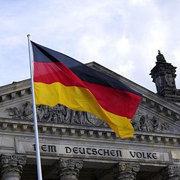 Symbolbild: Deutschland-Flagge mit Reichstagsgebäude im Hintergrund